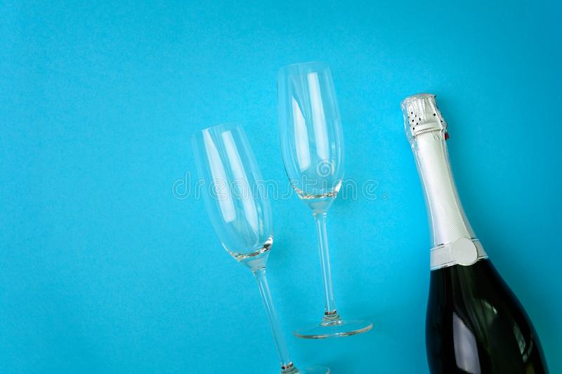 Wineglasses and bottle of champagne lying on blue paper background. New Year celebration concept. Top view. Flat lay royalty free stock image