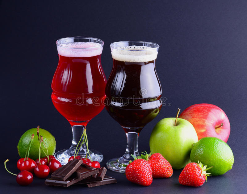 Wineglasses of craft beer with an assortment of fruits and berries over a black background. Beverage background with a copy space. stock photos