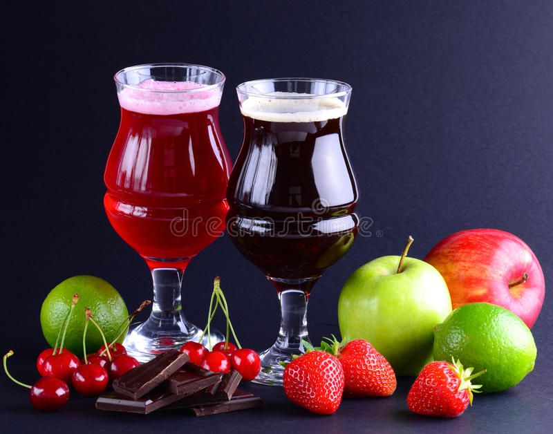 Wineglasses of craft sweet beer with an assortment over a black background. Beverage background with a copy space. stock photography