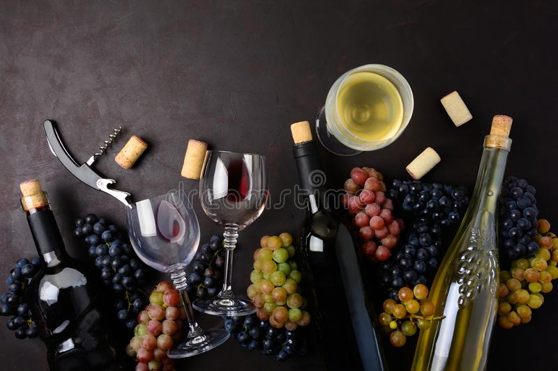 Wineglasses with red and white wine, bottles, grapes, corkscrew and corks lying on dark wooden background stock photography