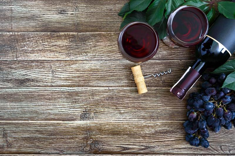 Wineglasses with red wine, bottle, corkscrew, blue grapes, leaves on a wooden table. Wine background with copy space. Top view, stock photography