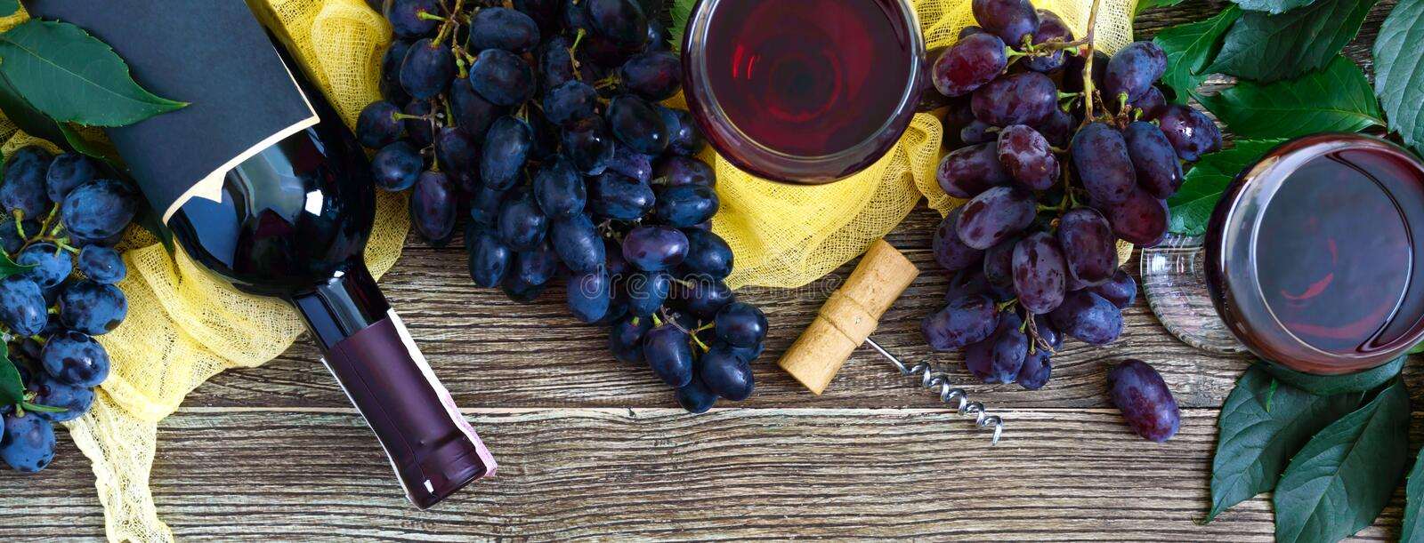 Wineglasses with red wine, bottle, corkscrew, blue grapes, leaves on a wooden table. Wine background with copy space. Top view, royalty free stock photo