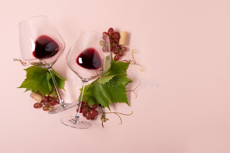 Wineglasses with red wine, grape, leaves and cork lying on pink background. Wine degustation concept. Flat lay. Top view. Copy. Space stock photography
