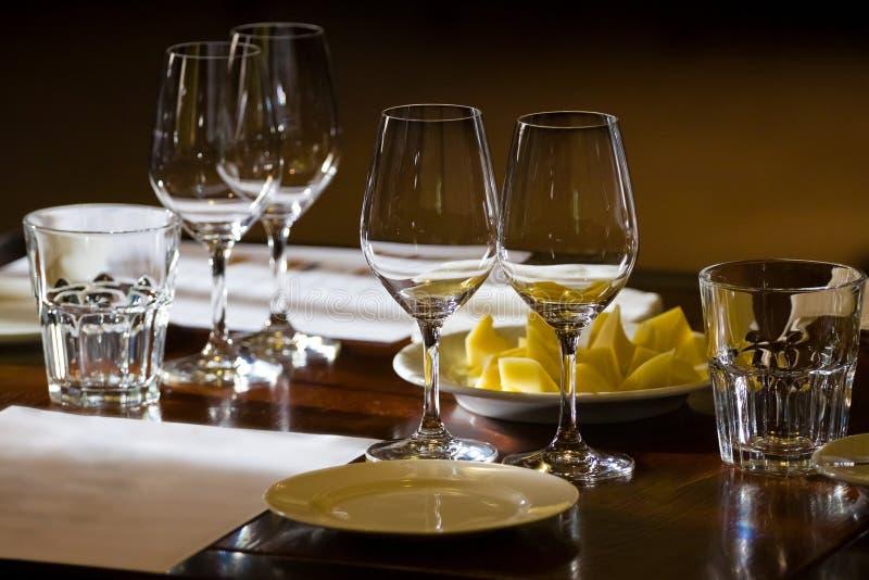 Wineglasses, szkła, talerze i ser na, zgłaszają gotowego dla wina testowanie w restauracji obraz royalty free