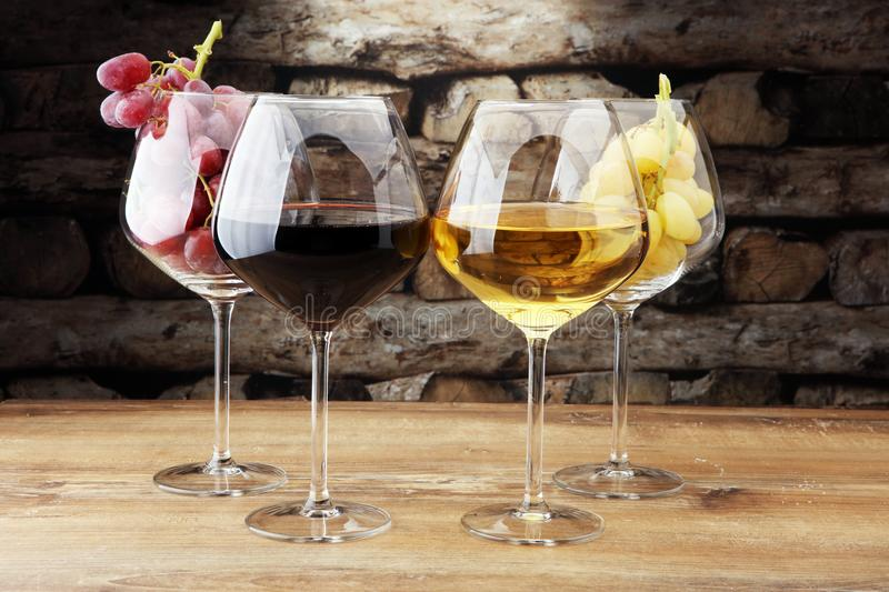 Wineglasses with white grapes and red grapes on wooden background. royalty free stock photography