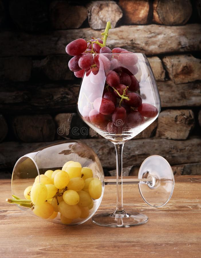 Wineglasses with white grapes and red grapes on wooden background. stock photo