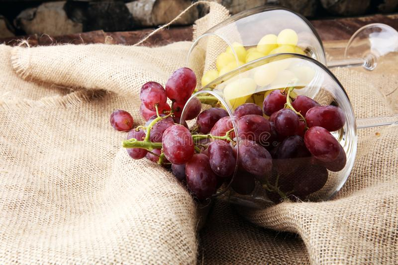 Wineglasses with white grapes and red grapes on wooden background. royalty free stock photo