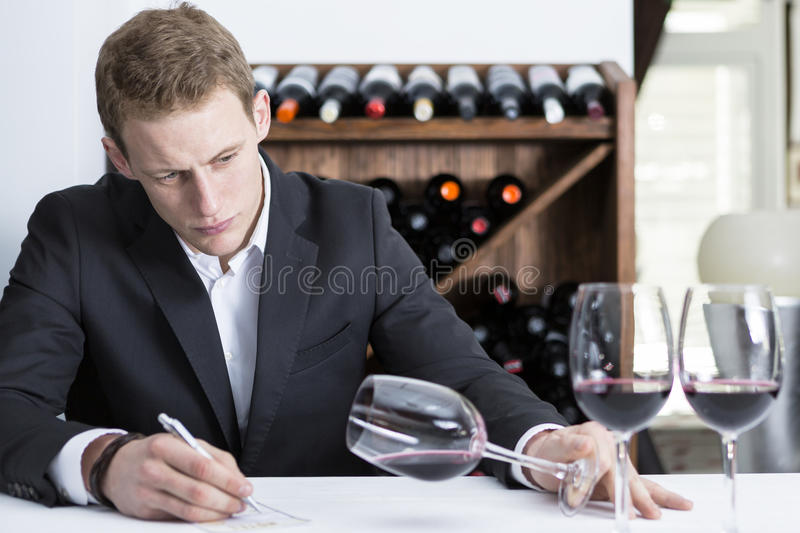 Winemaker examining a wine glass. Man on a wine tasting session on the visual phase is writing down in a wine tasting sheet at a restaurant stock images