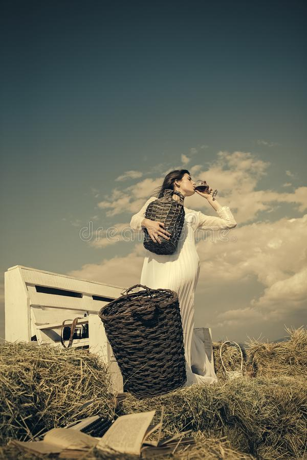 Winery tour concept. Woman in white dress drinking red wine on sunny day royalty free stock photos