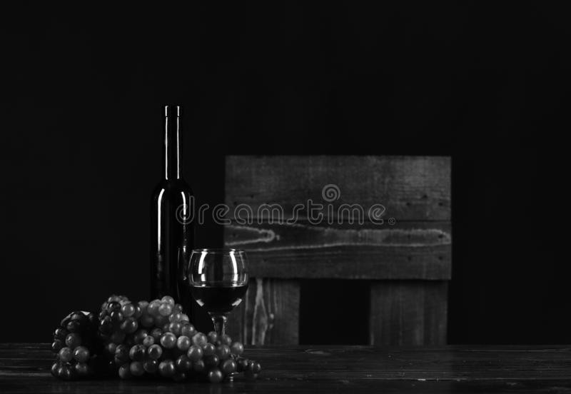 Winetasting and degustation still life concept. Set of dark grapes,. Black bottle and wineglass placed on table. Bordeaux or cabernet wine composition. Bottle royalty free stock photos