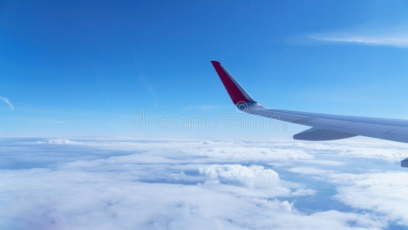 Wing of an airplane in the clouds stock photos