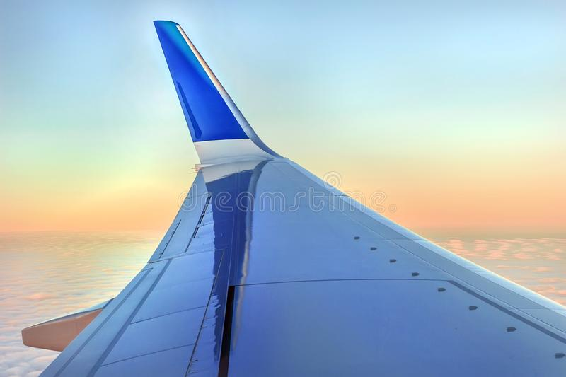 Wing of aircraft in dawn pink sky royalty free stock photo