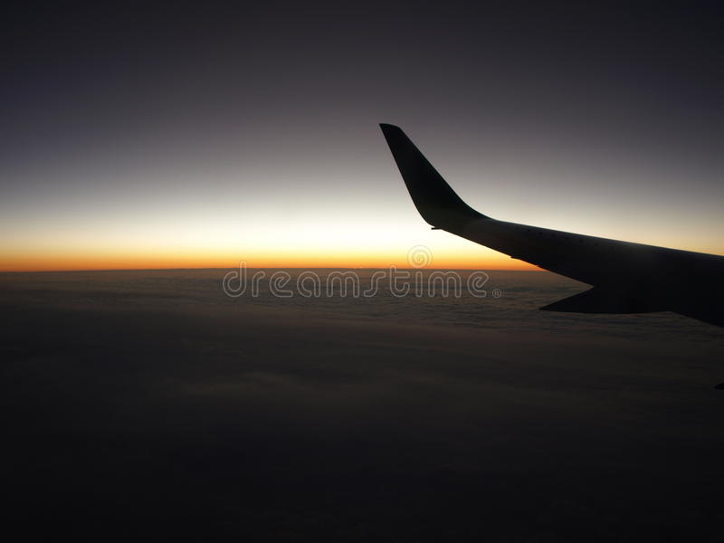 Wing of aircraft flying at dawn stock image