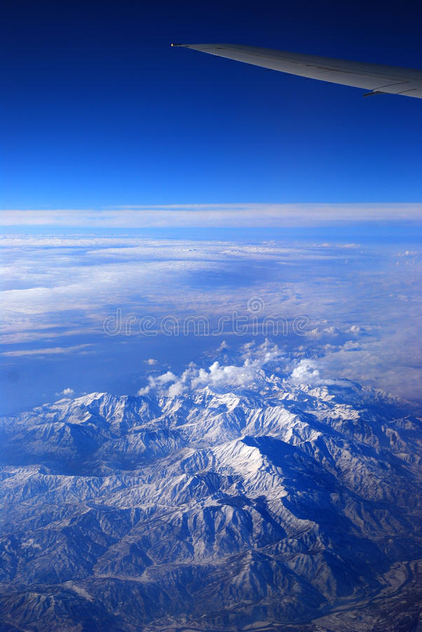 Wing of an airliner over the mountains stock photography