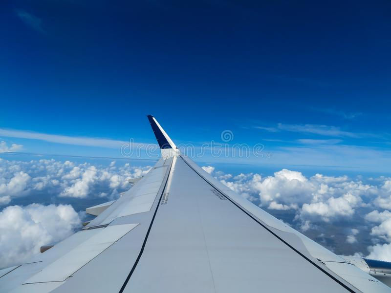 Wing of an airplane above the clouds stock images