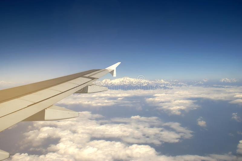 Wing of an Airplane Flying above the Cloud with View of Mount Everest Background, Travelling Concept royalty free stock photos
