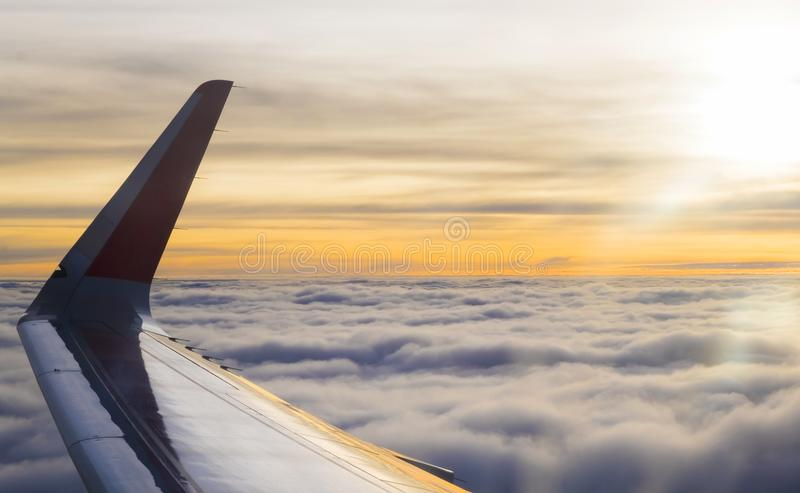Wing of airplane flying above clouds at beautiful sunset stock image
