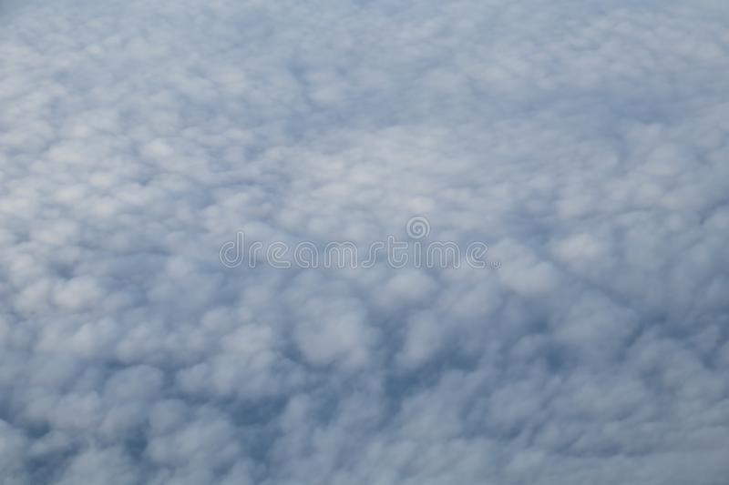 Wing of an airplane flying above the morning clouds and Andean mountain range. Aerial view from plane window with airplane wing and Andean mountain range below royalty free stock photography