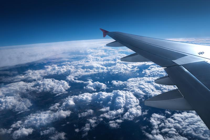Wing of an airplane flying above the sky with clouds and city land royalty free stock photo