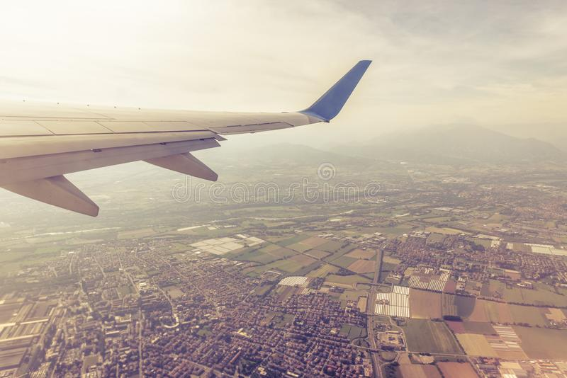 Wing of an airplane flying above towns and villages. The plane`s wing on the sky and earth background. Aerial panoramic view of motley land from airplane royalty free stock photos