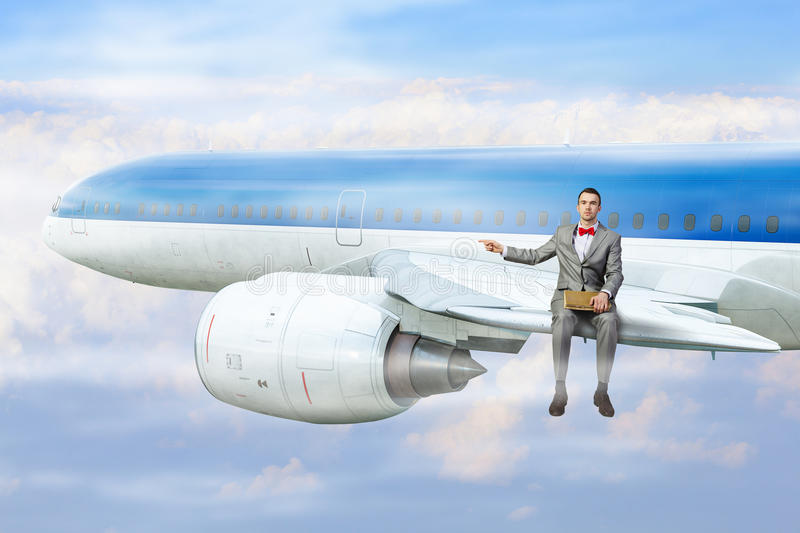 On wing of flying airplane . Mixed media. Young handsome businessman sitting on aiplane wing with old book in hands stock photography