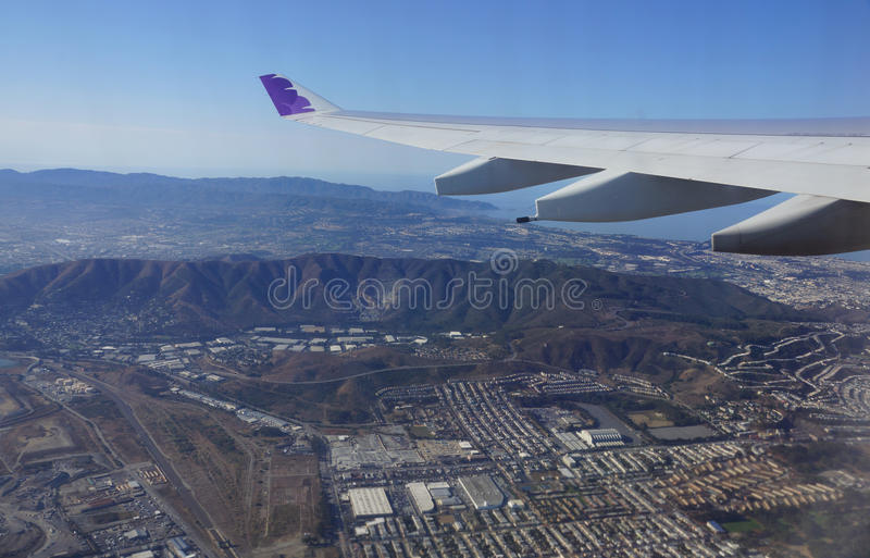 Wing of Hawaiian Airlines plane flying in the air above city royalty free stock photo