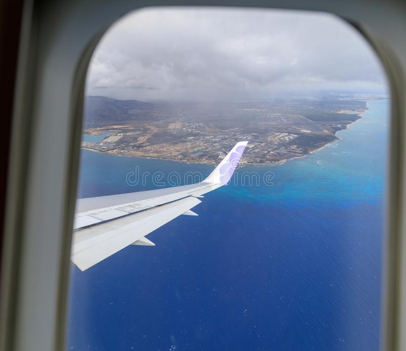 Wing of Hawaiian Airlines plane flying in the air above Honolulu royalty free stock image