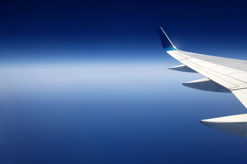 The wing of a jet passenger airliner. The wing of a jet passenger airliner on the background of a beautiful blue sky over the sea. Beautiful view took from the royalty free stock image
