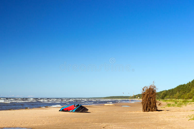 Wing for kite surfing on shore. Wing for kite surfing is dried on shore of Finnish Gulf in Estonian sea resort Narva-Joesuu. Kiting it`s aquatic sport, motion royalty free stock images