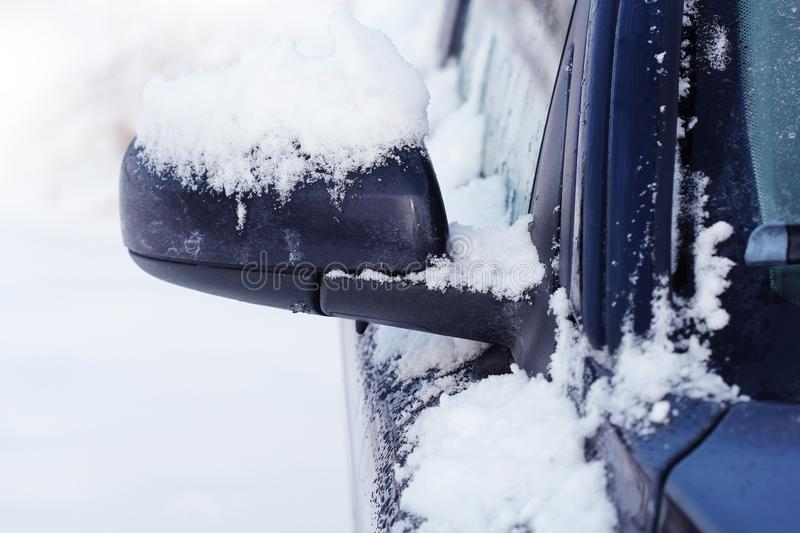 Wing mirror of car covered up with snow in winter time, close up royalty free stock image