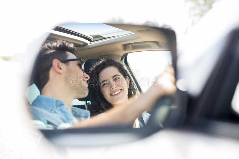 Wing mirror reflection of happy couple driving car stock image