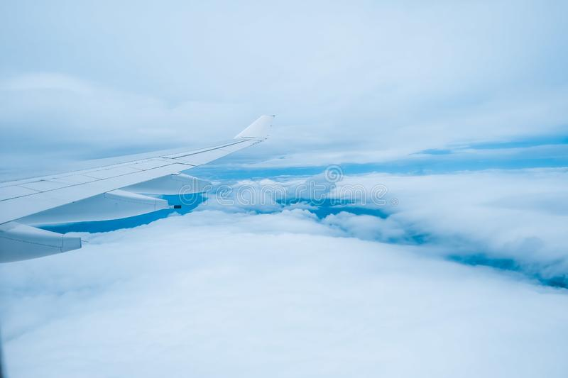 Wing of passenger jet flying between layers of white clouds. royalty free stock photography