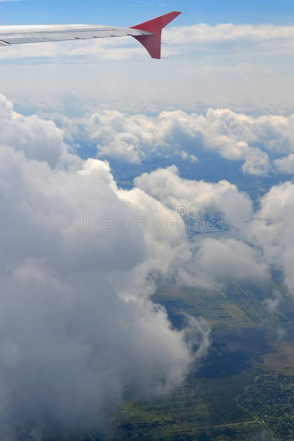 Wing of plane above cloudy sky in sunny day. Concept of travel, freedom, dreams, transport, eternity, hope. View from airplane. Illumination above the clouds royalty free stock photos