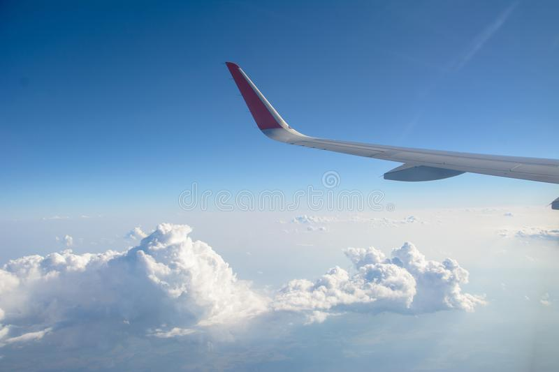 Wing of the plane on blue sky background, view from window of a jet plane wing with beautiful weather. stock images