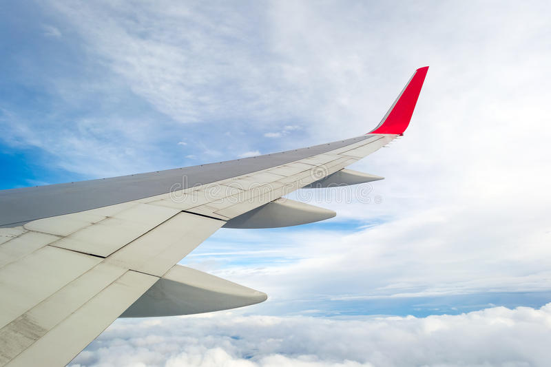 Wing of a plane, blue sky and clouds. stock photo