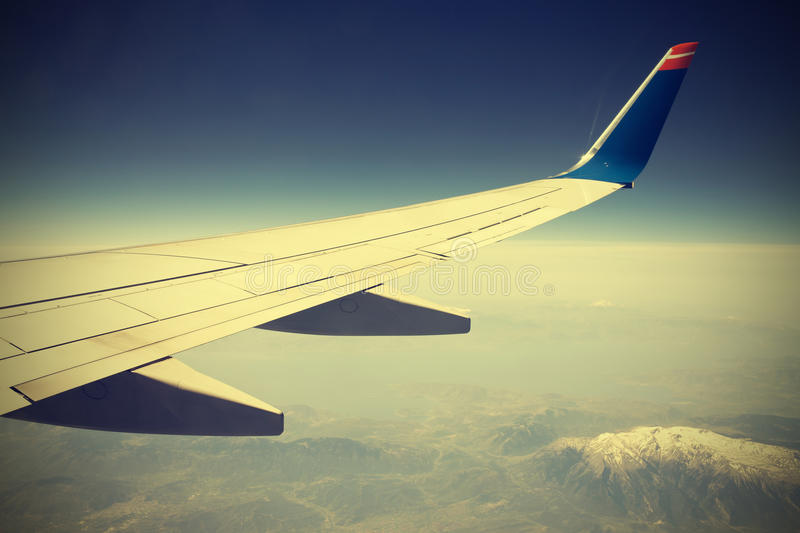 Wing of the plane on blue sky, instagram style. stock photos