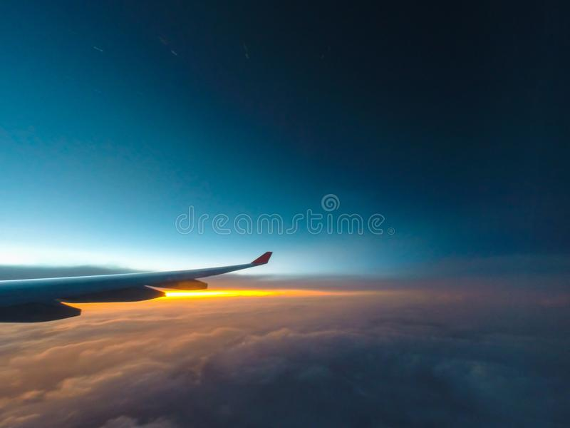 Wing of the plane with cloudy sky on background at sunrise stock photo