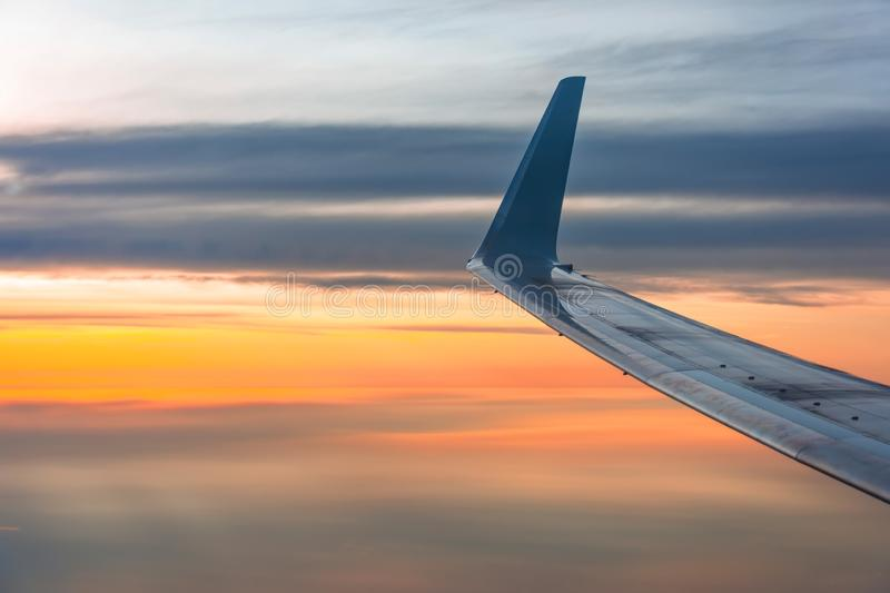 Wing of the plane lit by the sunrise on a background of sky royalty free stock photo