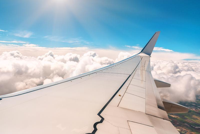 Wing of the plane over the clouds royalty free stock images
