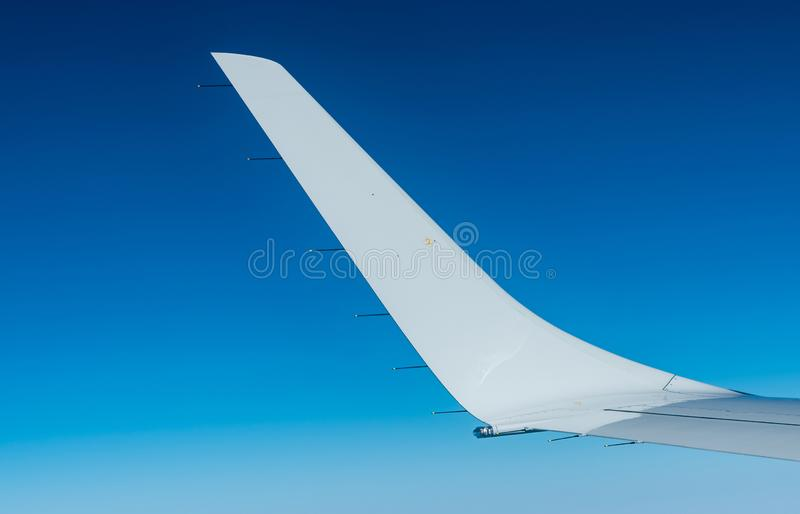 Wing of plane over white clouds. Airplane flying on clear blue sky. Scenic view from airplane window. Commercial airline flight. Plane wing above cloud. Flight royalty free stock image