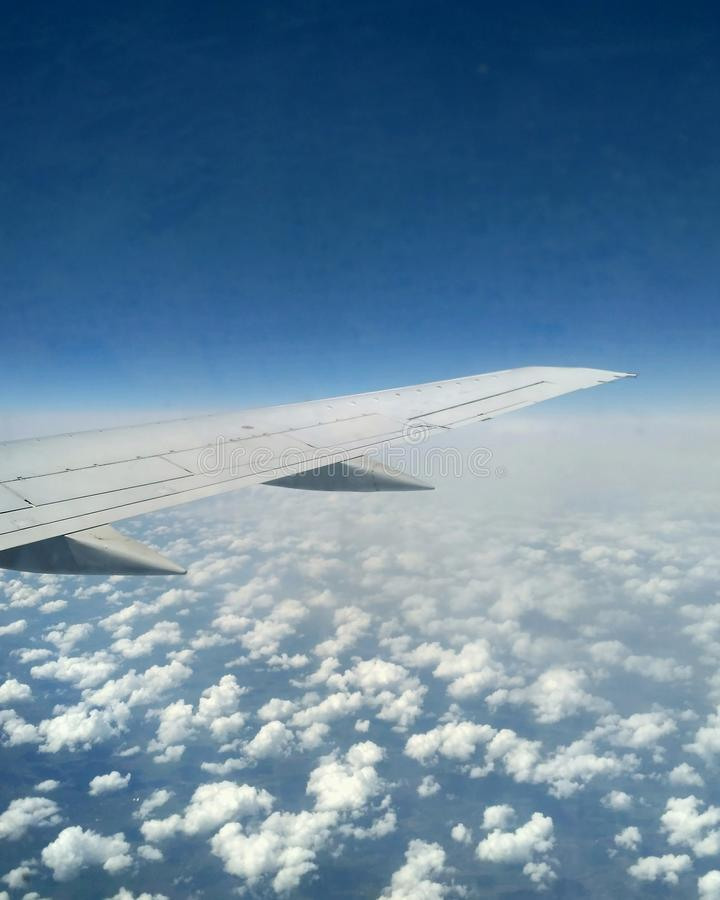 Wing of the plane in the sky with small clouds. View from the airplane`s window. Wing of the plane in the sky with clouds. View from the airplane`s window royalty free stock photography