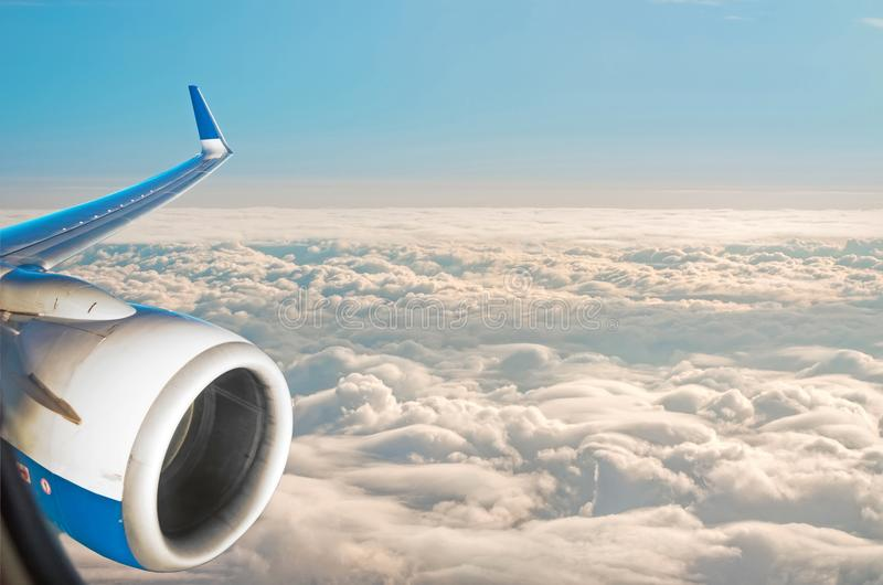 Wing view of the airplane on a winglets and jet engine, fluffy clouds on the skyline during climbing flight level. royalty free stock image