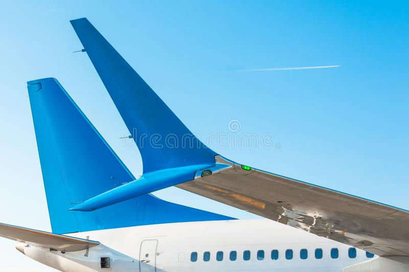 Winglets wings of the aircraft`s tail and fuselage against the blue sky with the airplane on the flight level. Winglets wings of the aircraft`s tail and stock photos