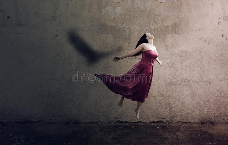 Wings like Eagles. A woman jumps up and her shadow is an eagle stock photography
