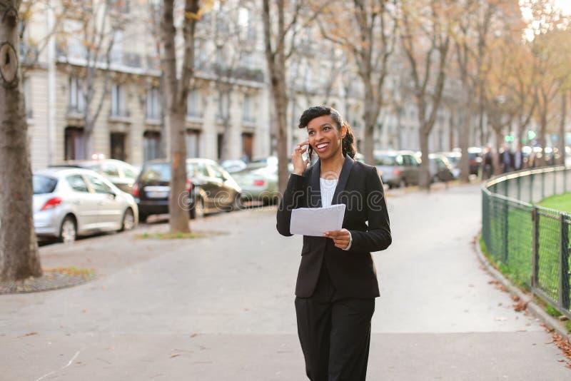 Winkeladviseur die met cliënten door smartphone en te lopen o spreken stock foto