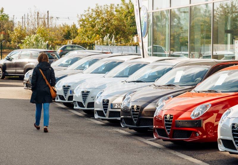 Winkelende nieuwe autovrouw die auto op een rij kiezen royalty-vrije stock fotografie