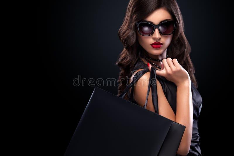 Winkelende vrouw die grijze die zak houden op donkere achtergrond in zwarte vrijdagvakantie wordt geïsoleerd royalty-vrije stock afbeeldingen