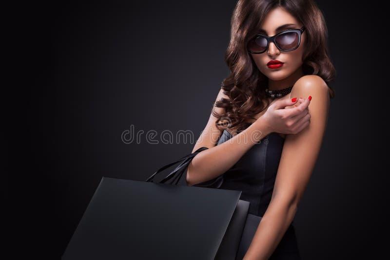 Winkelende vrouw die grijze die zak houden op donkere achtergrond in zwarte vrijdagvakantie wordt geïsoleerd stock afbeelding