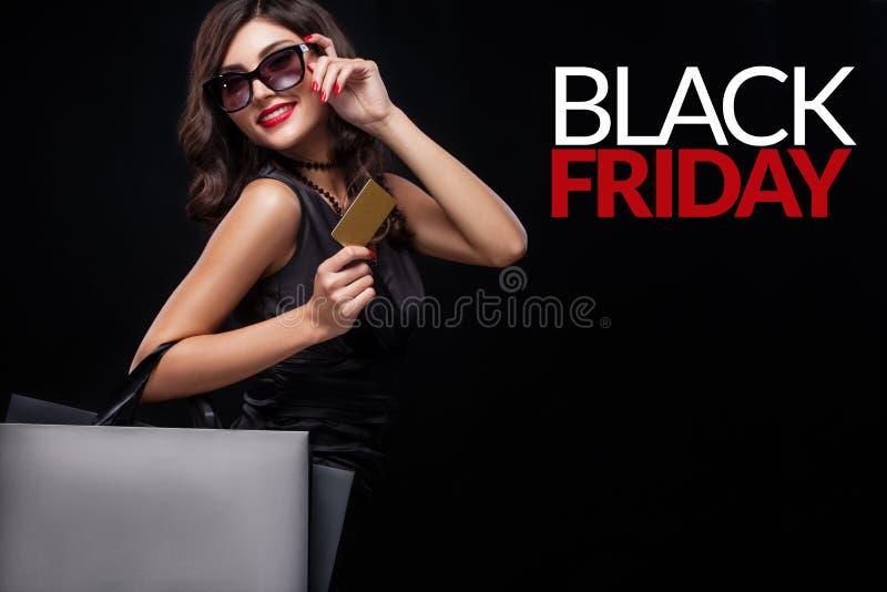 Winkelende vrouw die grijze zak op donkere achtergrond in zwarte vrijdagvakantie houden royalty-vrije stock fotografie