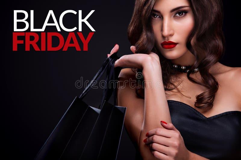 Winkelende vrouw die grijze zak op donkere achtergrond in zwarte vrijdagvakantie houden royalty-vrije stock foto
